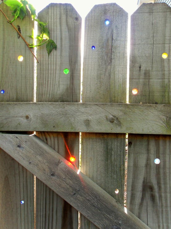 Place marbles in to holes in a fence for a sparkling light show when the sun hits the color