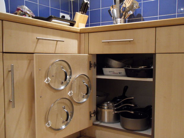 Hang pot and pan lids on the cabinet door by using adhesive hooks
