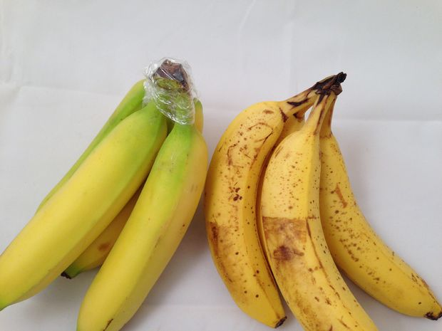 Secure plastic wrap around a bunch of bananas to slow the ripening process