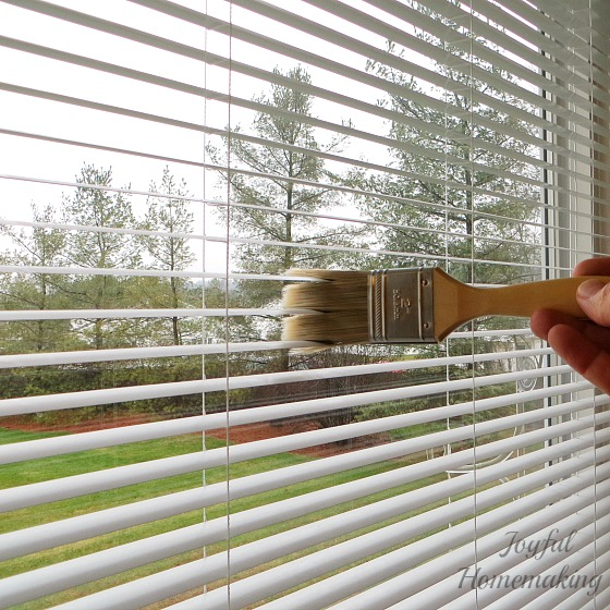 Use a paintbrush to clean blinds